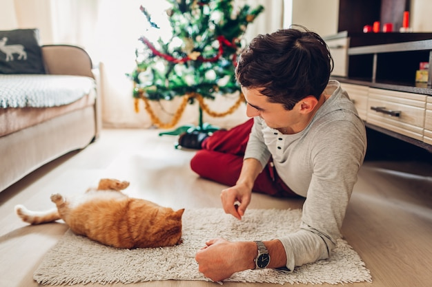 Young man lying by christmas tree and playing with cat at home. new year concept