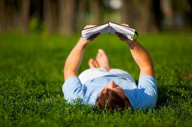 Young man lying on green grass and reading book