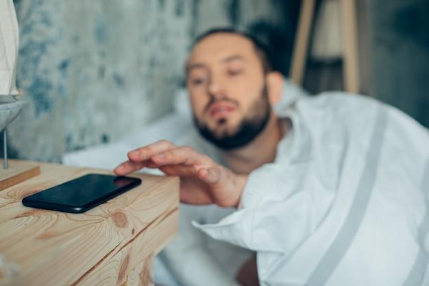아침에 침대에 누워 휴대폰의 알람 시계를 끄는 청년