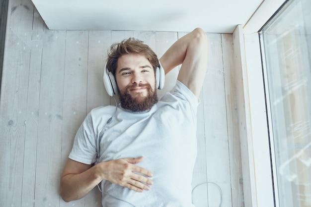 ヘッドフォン技術を身に着けている窓の近くに横たわっている若い男