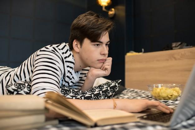 Молодой человек лежал на кровати, используя ноутбук