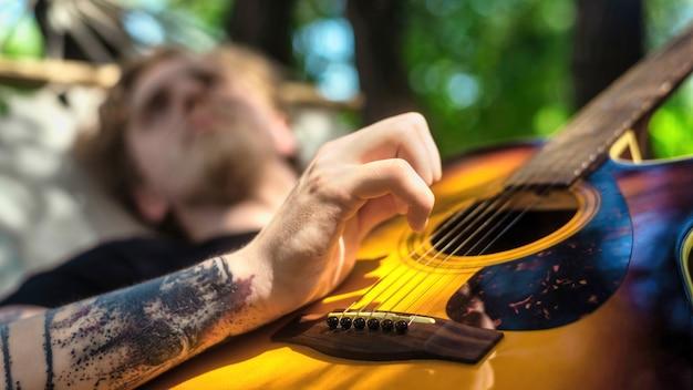 해먹에 누워 있는 젊은 남자가 기타를 치고 있다. 주변의 녹지. 글램핑