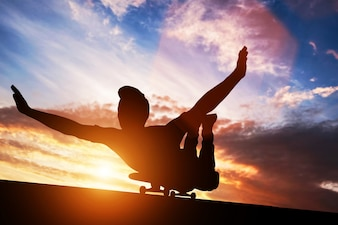 Young man lying on skateboard at sunset.