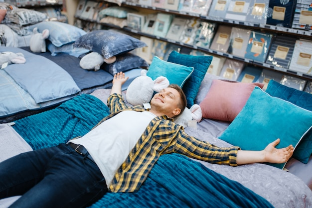 寝具店のベッドに横になっている若い男。市場で家庭用品を購入する男性の人、店で寝ている男