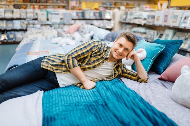 寝具店のベッドに横になっている若い男