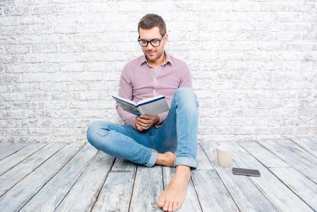 床に横になって本を読んでいる若い男