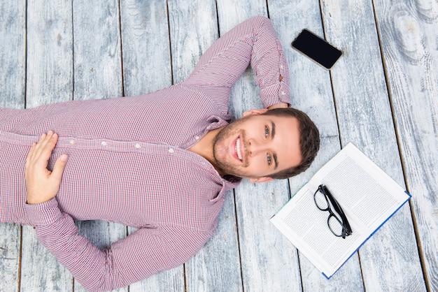 本を持って床に横たわっている若い男