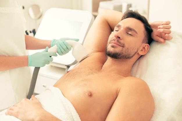 Молодой человек, лежа на медицинской кушетке с закрытыми глазами и улыбаясь, проходит процедуру лазерной эпиляции в подмышечной впадине