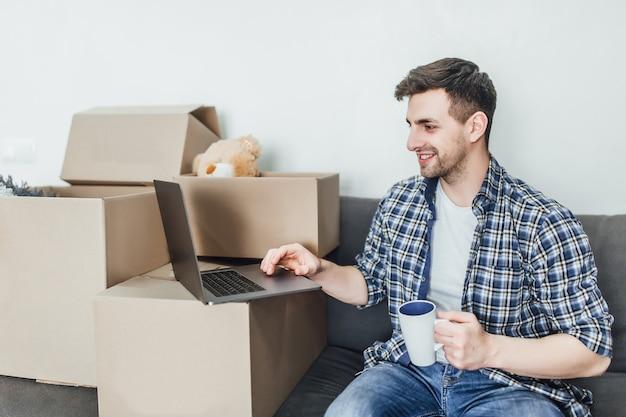 近くに梱包箱を置いてソファに横になり、ラップトップで次の必要なものを計画している若い男