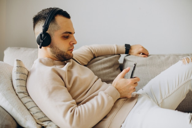 Giovane uomo sdraiato sul divano ascoltando musica in cuffia