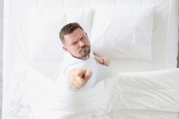 Young man lying in white bed and showing index finger up top view
