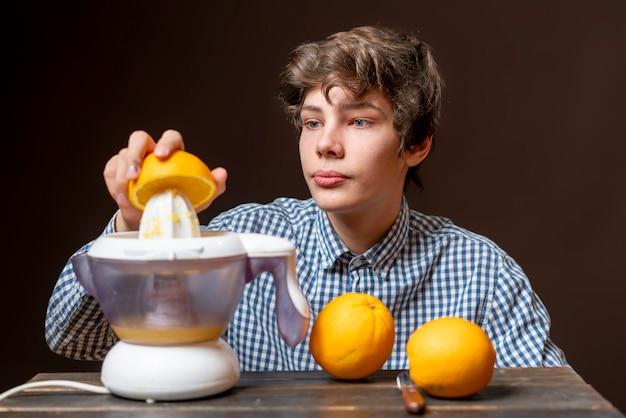 若い男は新鮮なオレンジbでジュースを作る