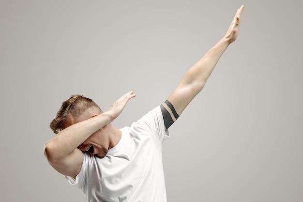 젊은 남자가 회색 공간에 그의 팔로 댑 운동을합니다.