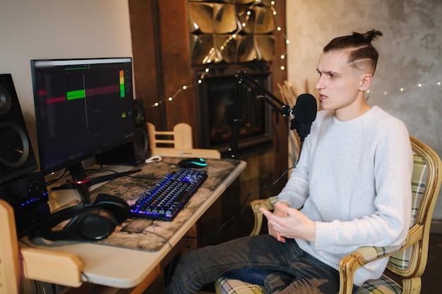 젊은 남자가 pc와 두 개의 전문 마이크를 사용하여 집에서 팟 캐스트 오디오 녹음을 만듭니다.