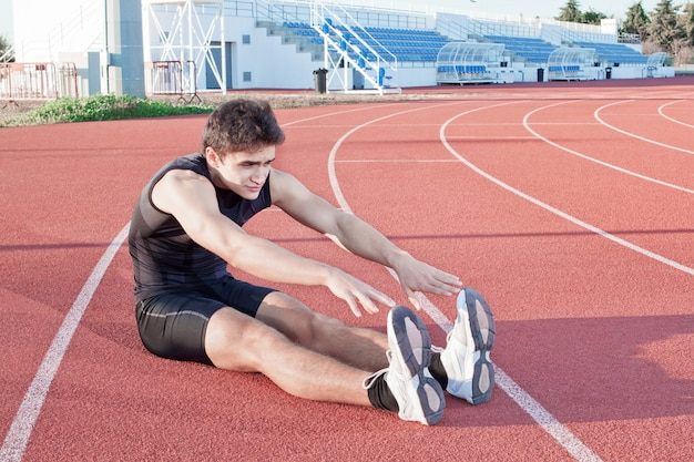 A young man makes an athlete stretching. against the background the stadium.