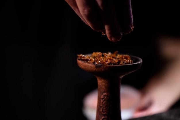Young man makes hookah. barman fills black burnt ceramic bowl for hookah smoking different types of tobacco.