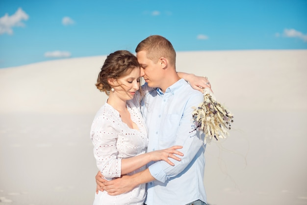 Young man makes marriage proposal to his girlfriend for a romantic date in the open air in the sand dunes.