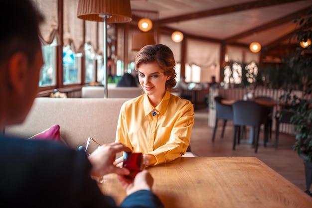 Молодой человек делает предложение руки и сердца красивой женщине в роскошном ресторане. романтическое свидание пары