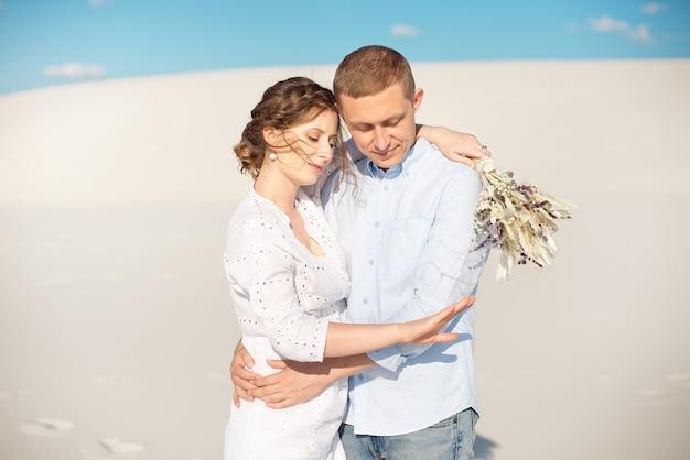 若い男は彼のガールフレンドに砂丘の野外でロマンチックなデートのための結婚の提案をします。