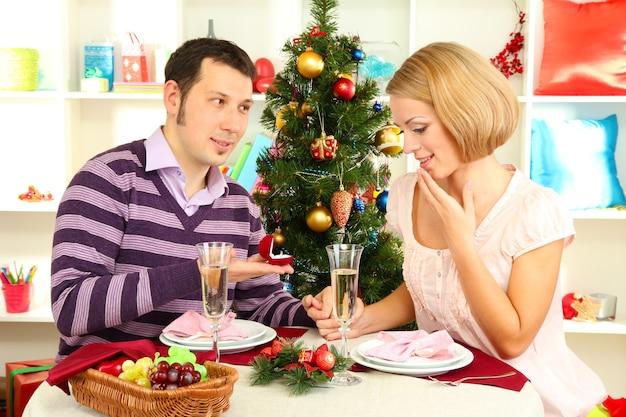 若い男がクリスマスツリーの近くのテーブルで女の子とプロポーズする