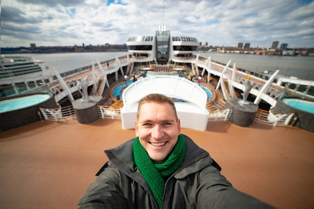 Young man makes selfie with huge cruise ship and city on background. concept of happy vacation and travelling.