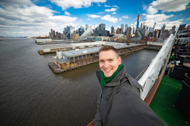 Young man makes selfie with huge cruise ship and new york city on background. concept of happy vacation and travelling.