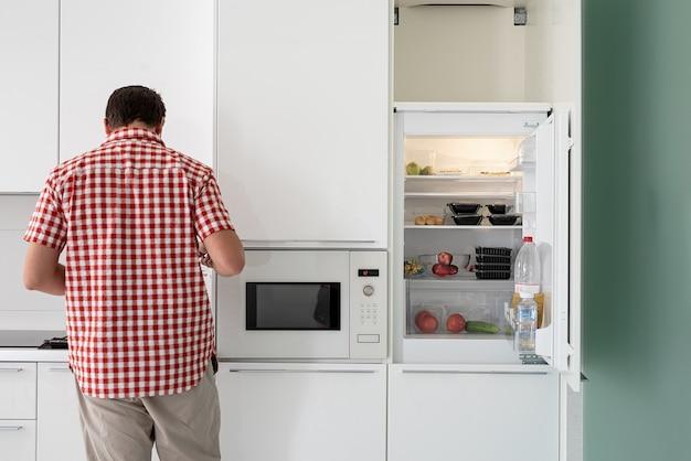 Молодой человек делает чай, стоя рядом с открытым холодильником.