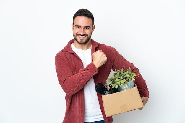 Молодой человек делает ход, поднимая коробку, полную вещей, изолированную на белой стене, празднует победу
