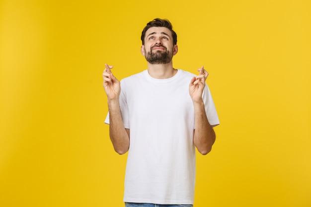 Молодой человек, делая желание, изолированные на желтом