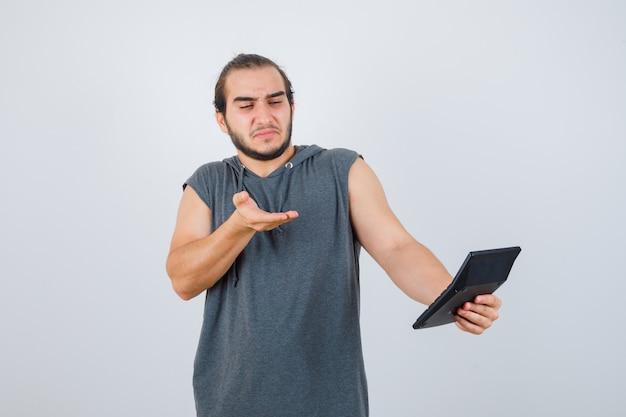 パーカーで質問ジェスチャーをしている若い男と不機嫌そうな正面図。