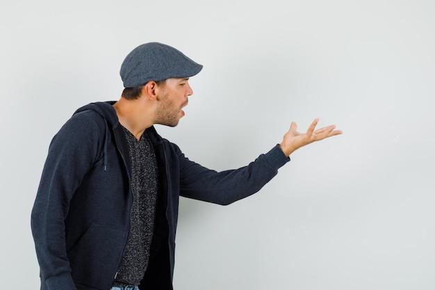 Молодой человек делает жест вопроса в футболке, куртке, кепке и выглядит нервным.