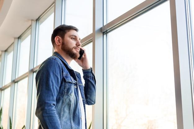 カジュアルなジージャンの窓の壁の近くの屋内で電話で話しているビジネス電話をかける若い男。現代の市役所の賢い人は、モバイル会話をしています。白人のひげを生やしたビジネスマン。