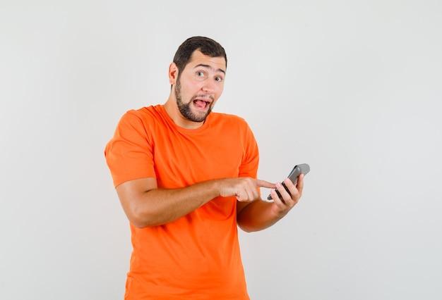 オレンジ色のtシャツの正面図で電卓で計算を行う若い男。