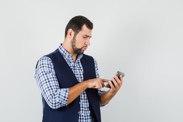 シャツの電卓で計算をする若い男
