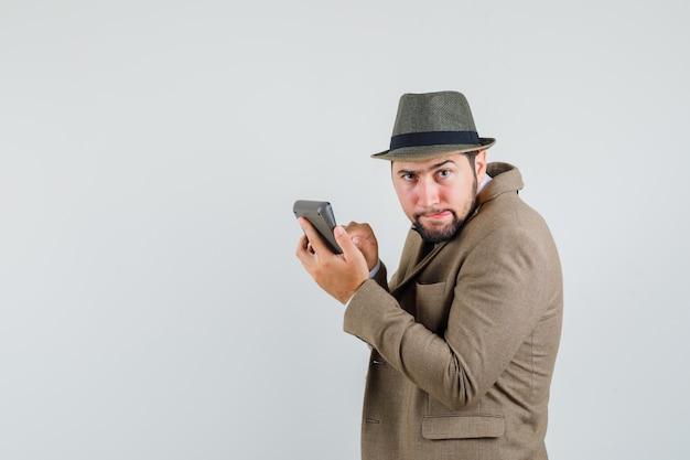 スーツ、帽子、全知に見える電卓で計算を行う若い男。 。