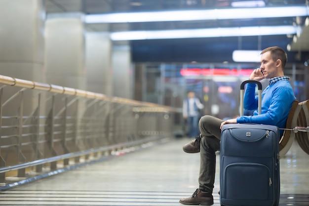 공항에서 전화를 만드는 젊은 남자