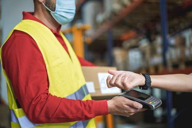 Young man making contactless payment inside warehouse store during coronavirus outbreak - focus on smart watch