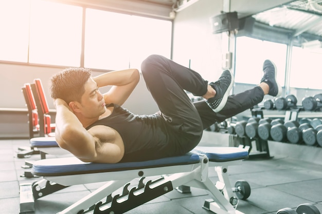 Young man making exercise, sit-ups and cross crunches for abs muscles in fitness club or g