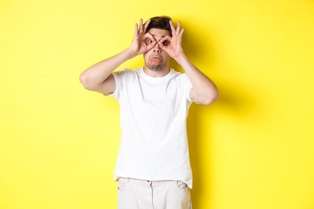 재미 있은 얼굴을 만들고 혀를 보여주는 젊은 남자, 노란색 벽에 흰색 티셔츠에 서있는 바보