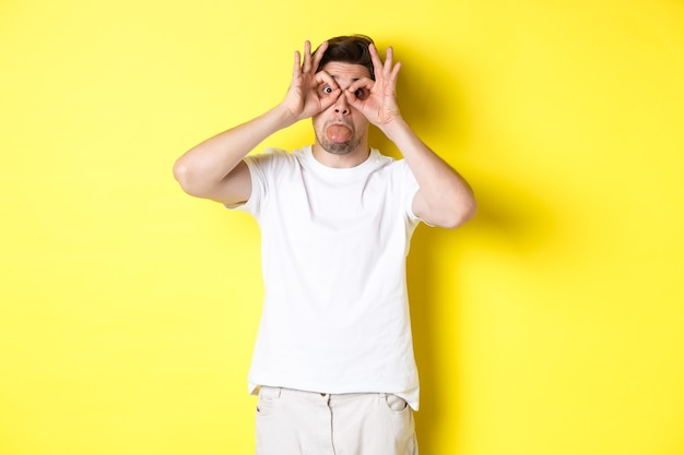 Young man making funny faces and showing tongue, fool around, standing in white t-shirt against yellow background