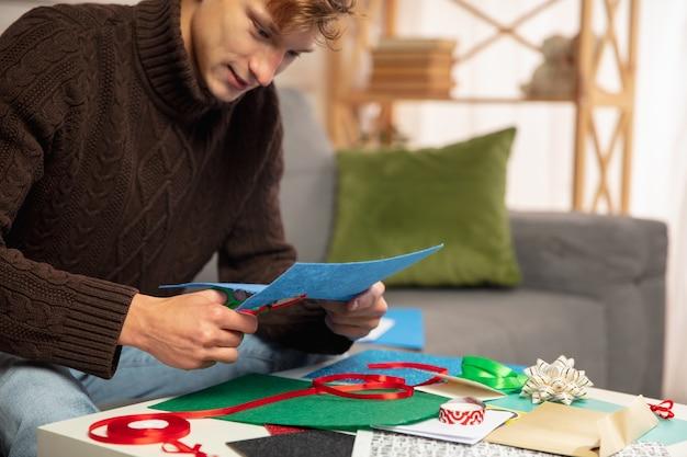 Молодой человек делает поздравительную открытку на новый год и рождество 2021 года для друзей или семьи, бронирование лома, сделай сам. написав письмо с наилучшими пожеланиями, создайте его самодельную открытку. праздники, торжество.