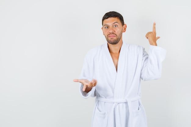 白いバスローブで銃のジェスチャーをし、困惑しているように見える若い男、正面図。