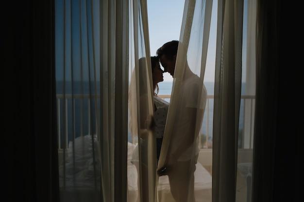 朝のカーテンの後ろのバルコニーに立っている彼の魅力的なガールフレンドに愛の告白をする若い男。忙しい一日の終わりにテラスでキス美しいカップルの肖像画