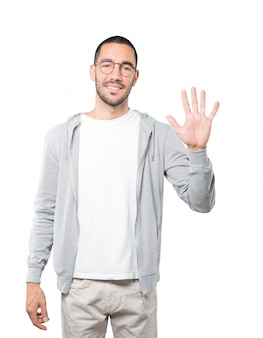 Young man making a number five gesture