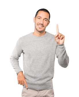 Young man making a number one gesture