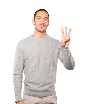 Young man making a number three gesture