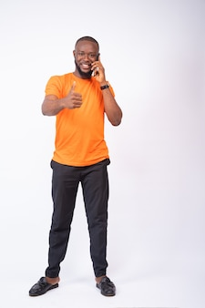 Young man making a phone call and thumbs up isolated on a white wall