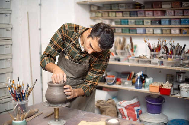 Young man making pottery in workshop