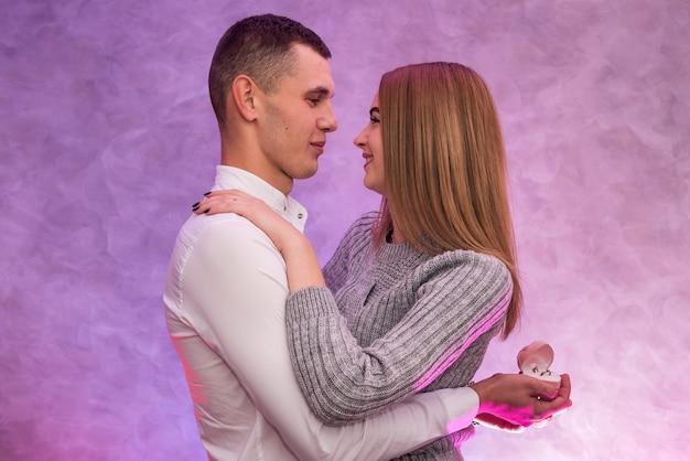 彼の女の子にダイヤモンドと金の指輪で提案をしている若い男。バレンタインのサプライズ