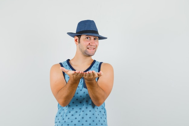 젊은 남자가 파란색 중항, 모자에 제스처를 받거나주고 쾌활한 찾고